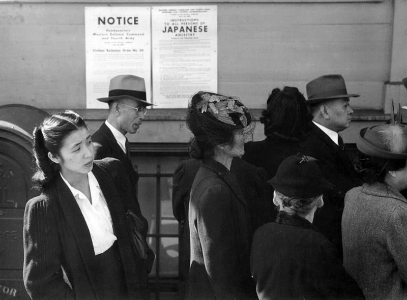 Japanese Americans in front of poster with internment orders. • Photo courtesy of the U.S. Department of the Interior