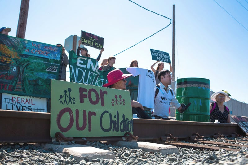 On Monday, July 28, three residents of Anacortesand	Seattle blockaded the oil train facility at Tesoro's Anacortes Refinery by locking their bodies to barrels full of concrete. • Photo courtesy of Rising Tide Seattle