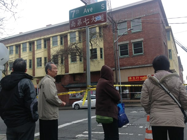 Neighborhood residents observe the 665 S King St building on Christmas morning, December 25, 2013. • Photo by Dean Wong