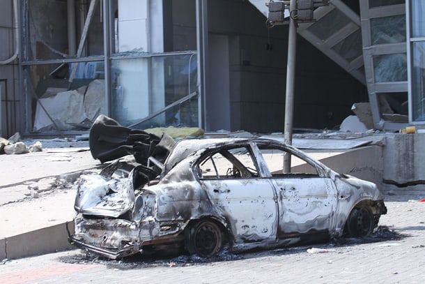 The scene of the Tianjin explosion, showing smashed windows and a smashed and burned car. • Photo by Voice of America