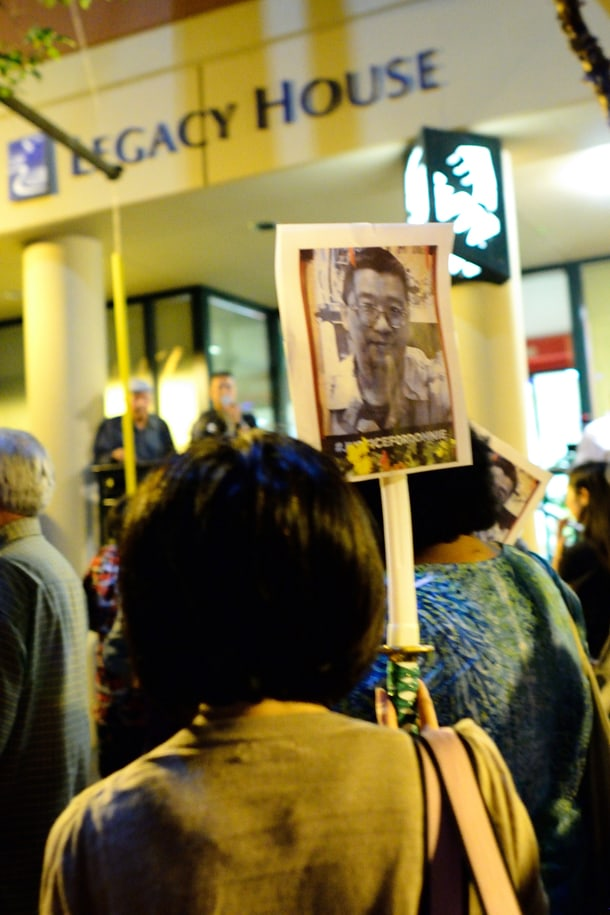 A protestor holds a sign featuring an image of Donnie Chin at the second nonviolent protest on July 31. • Photo by Isaac Liu
