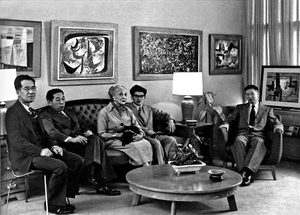 Art dealer Zoe Dusanne shares her antique couch with George Tsutakawa and John Matsudaira, left and right, while to the sides in modern chairs are Paul Horiuchi, left, and Kenjiro Nomura, right. They are the quartet of Japanese-American artists Dusanne exhibited together in her gallery in 1952, the year also that Elmer Ogawa took this group portrait of them. • Photo by Elmer Ogawa.