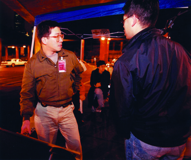 """Donnie Chin, left, and volunteers provide a watchful eye at a Jackson Street parking lot during """"Las Vegas Night"""" on November 24, 1999. Chin, director of the International District Emergency Center, had given assistance to neighborhood residents since 1968. • Photo by John Lok"""
